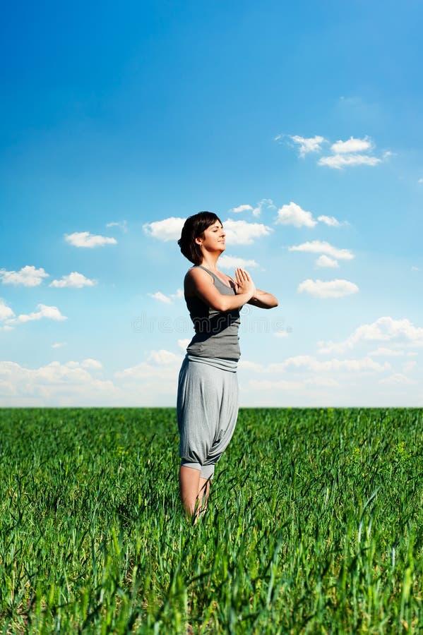 Übendes Yoga der jungen Frau und Entspannung am Sommer lizenzfreies stockfoto