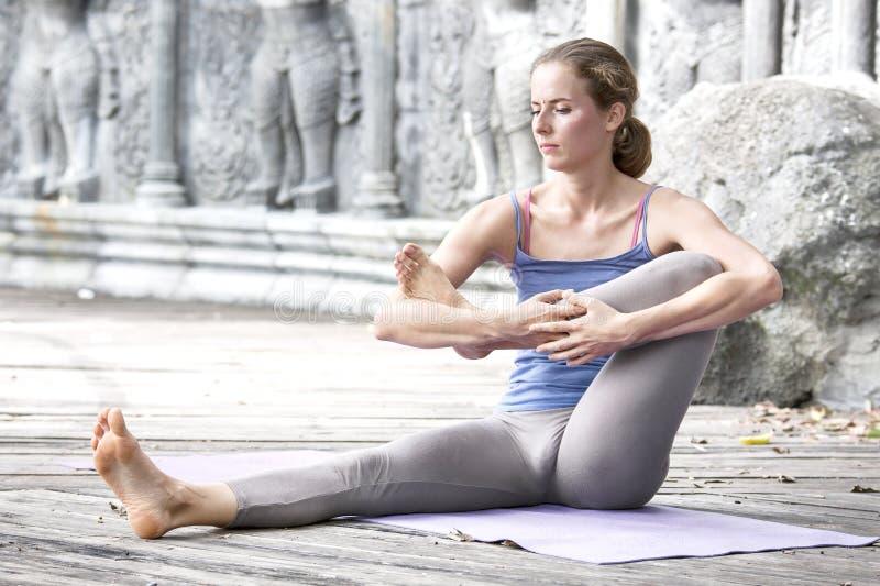 Übendes Yoga der jungen Frau während des Yogarückzugs in Asien, Bali, Meditation, Entspannung in verlassenem Tempel lizenzfreie stockfotos