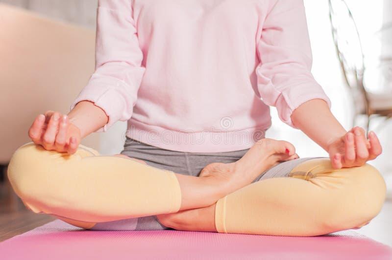 Übendes Yoga der jungen Frau, zu Hause meditierend in Lotussitz stockfoto