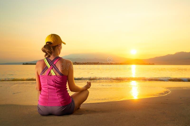 Übendes Yoga der jungen gesunden Frau auf dem Strand bei Sonnenuntergang lizenzfreies stockfoto