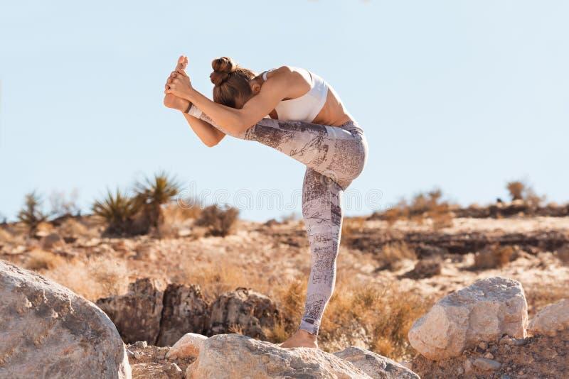 Übendes Yoga der jungen Jogifrau in der Wüste vor einem Sonnenuntergang stockbild