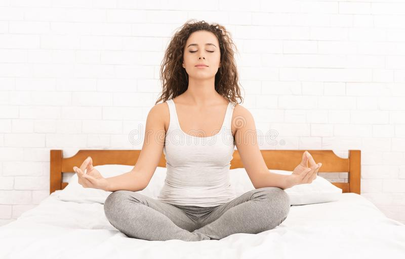 Übendes Yoga der jungen kaukasischen Frau im Bett lizenzfreies stockbild