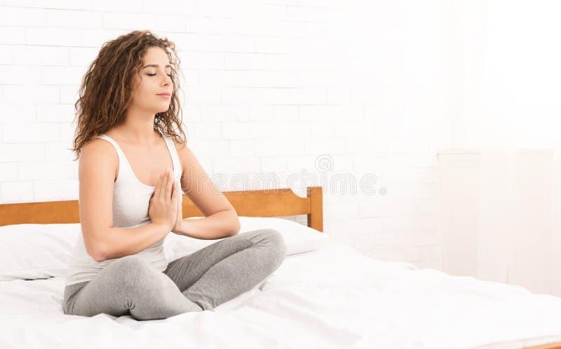 Übendes Yoga der jungen kaukasischen Frau im Bett stockfoto