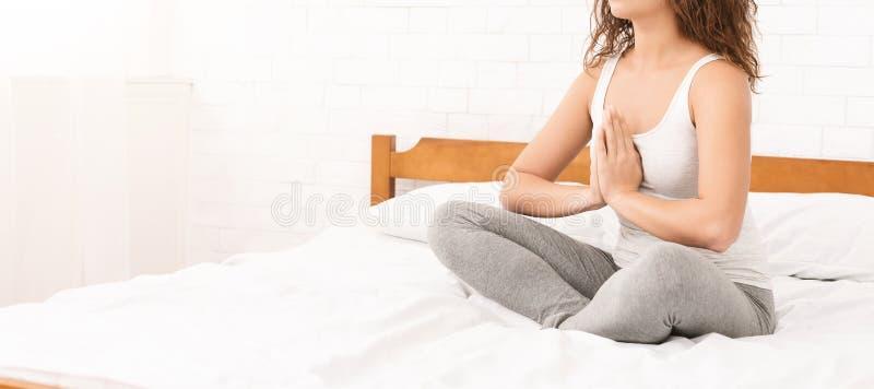 Übendes Yoga der jungen kaukasischen Frau im Bett lizenzfreie stockfotos