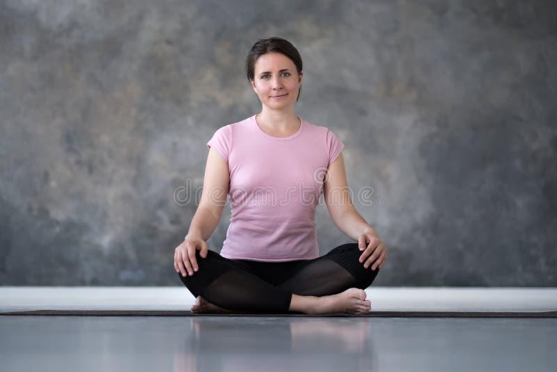 Übendes Yoga der jungen kaukasischen Frau, Sukhasana-Übung tuend, einfache Seat-Haltung stockbild