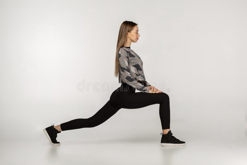 Übendes Yoga der jungen sportlichen attraktiven Frau, das Rückkriegersübung tut stockfotos