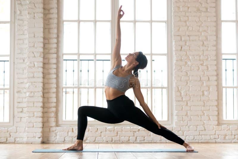 Übendes Yoga der jungen sportlichen attraktiven Frau, Rückkrieg tuend lizenzfreies stockbild
