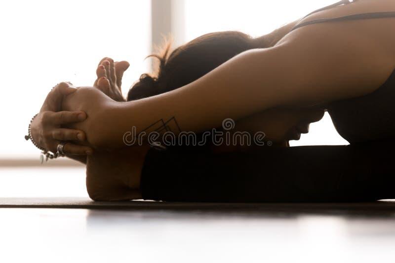 Übendes Yoga der jungen sportlichen Frau, paschimottanasana Haltung, clos lizenzfreie stockfotos
