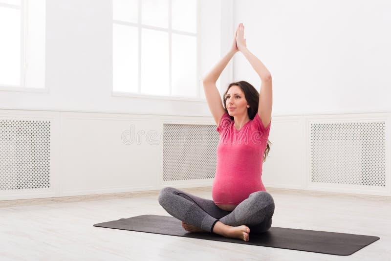 Übendes Yoga der schwangeren Frau zu Hause stockfoto