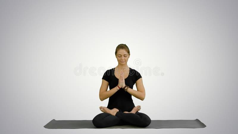 Übendes Yoga der sportlichen attraktiven Frau, sitzend in voller Lotus-Übung, Siddhasana-Haltung und arbeiten auf Weiß aus lizenzfreies stockfoto