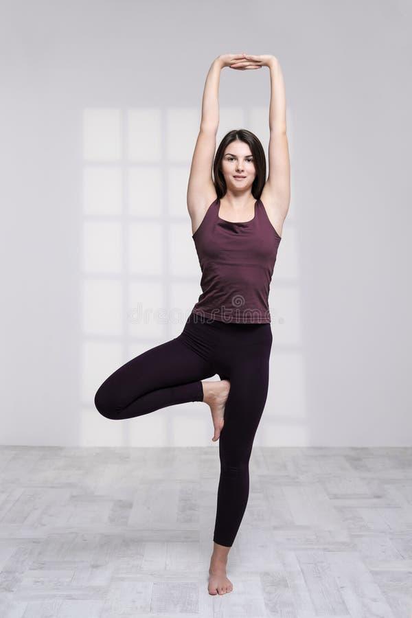 Übendes Yoga der sportlichen Frau auf weißem Hintergrund lizenzfreie stockfotos