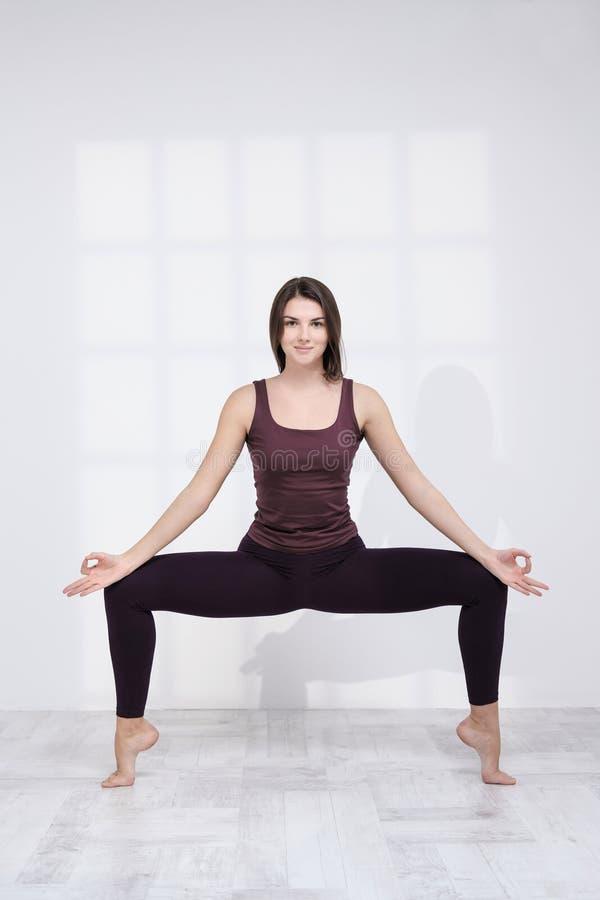 Übendes Yoga der sportlichen Frau auf weißem Hintergrund lizenzfreie stockfotografie