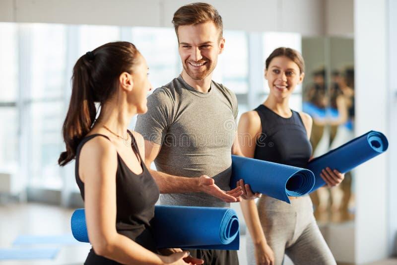 Übendes Yoga des gut aussehenden Mannes mit Mädchen stockbild