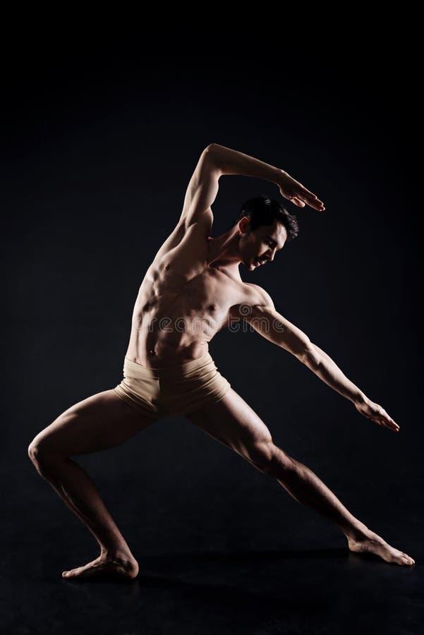 Übendes Yoga des gutaussehenden Mannes in der Dunkelheit beleuchtete Studio lizenzfreies stockfoto