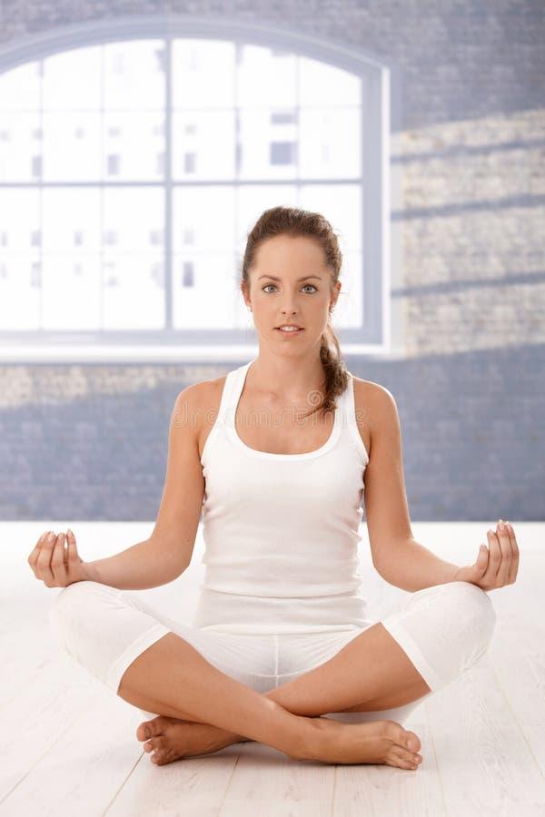 Übendes Yoga des hübschen Mädchens im Studio stockbilder