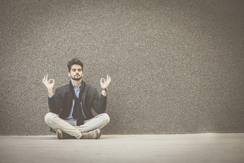 Übendes Yoga des jungen Geschäftsmannes auf Bürgersteig stockfotografie