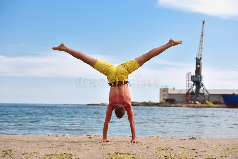 Übendes Yoga des jungen Mannes auf Strand stockfoto