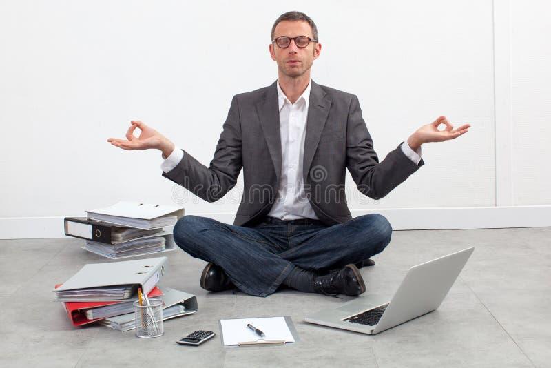 Übendes Yoga des ruhigen Unternehmers auf dem Büroboden lizenzfreie stockfotografie