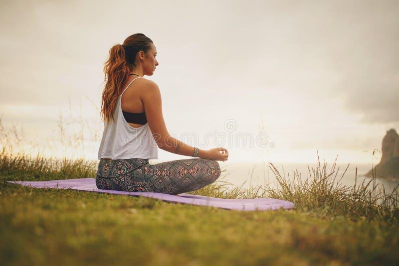 Übendes Yoga des weiblichen Modells der Eignung stockbild