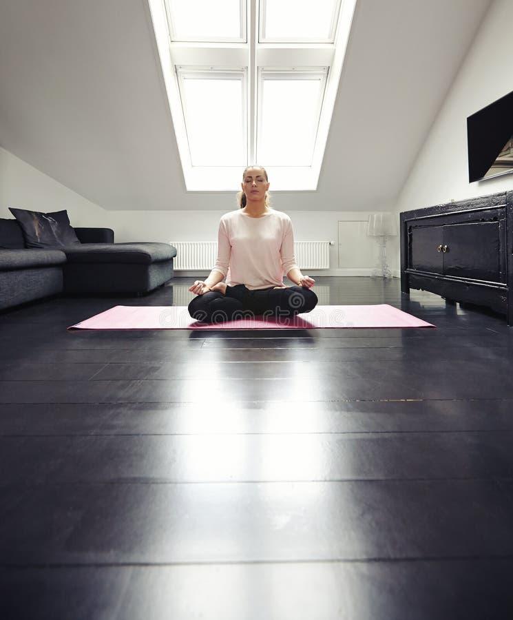 Übendes Yoga junger Dame in ihrem Wohnzimmer stockfotografie
