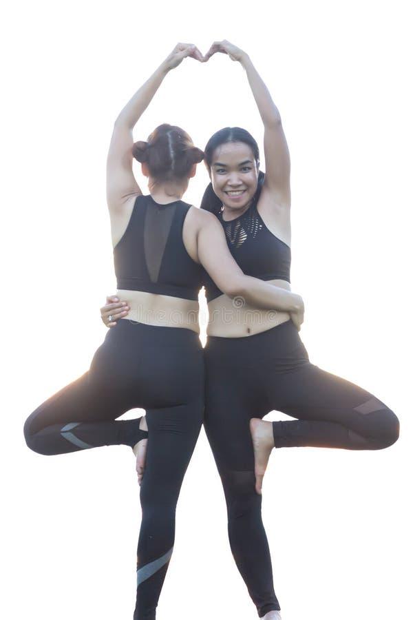 Übendes Yoga von zwei Frau auf dem Boden mit weißem Hintergrund lizenzfreie stockbilder