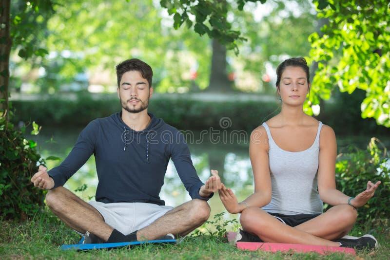 ?bendes Yoga Yougn-Paare in der Natur stockbilder