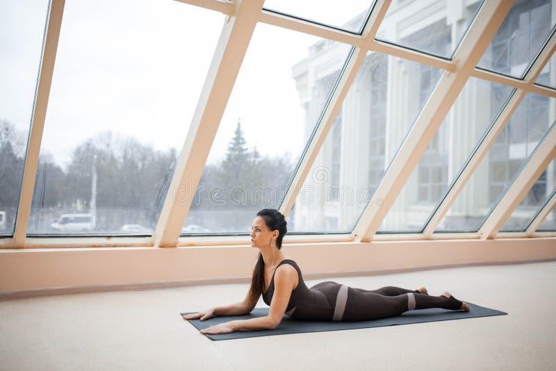 Übendes Yogakonzept der Brunettefrau, dehnend in Kobraübung, Bhujangasana-Haltung vor großen Fenstern aus Ausarbeiten, fu stockbilder