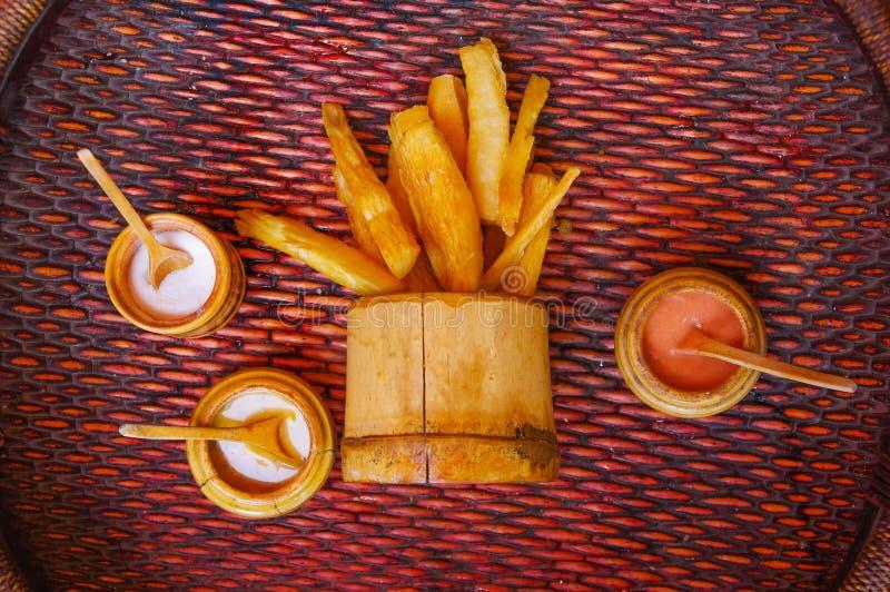 Über Ansicht des köstlichen gebratenen Yuccas innerhalb einer hölzernen Schüssel mit sortierten Soßen, über einem Holztisch stockfotografie