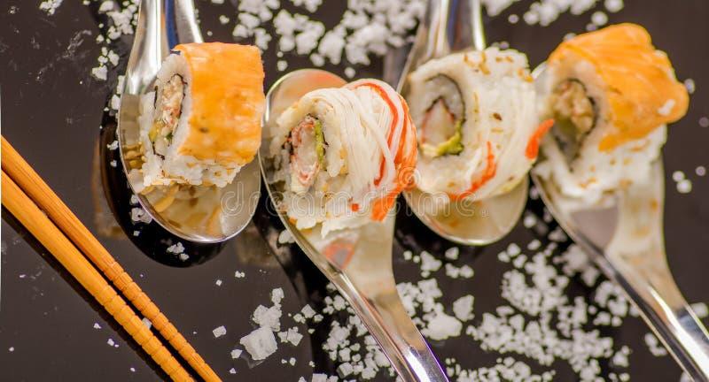 Über Ansicht von köstlichen Sushi rollt einen vorbei metallischen Löffel und Bambusessstäbchen mit dem kleinen Salzkorn, das an g stockbild