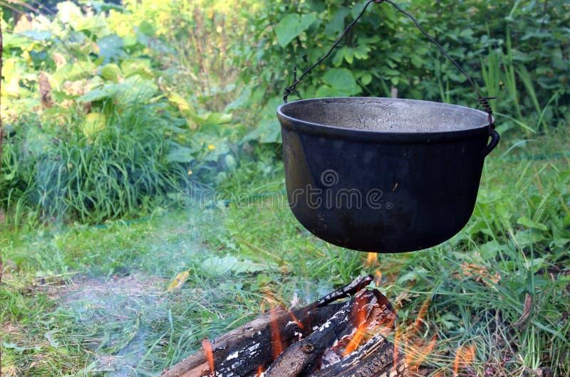 Über dem Feuer hängt eine kochende Schüssel lizenzfreie stockbilder