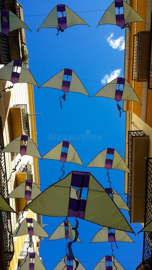 Über der schmalen Straße in Reus zwischen hohen Häusern gibt es ausgedehnte Fahnen in Form von gelben Drachen gegen stockfotografie