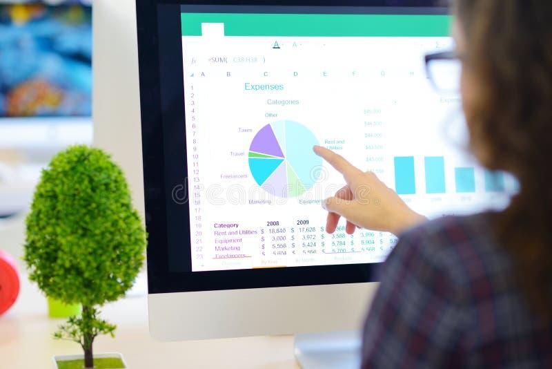 Über der Schulteransicht einer Geschäftsfrau, die am Computer arbeitet und auf Diagramm zeigt lizenzfreie stockbilder