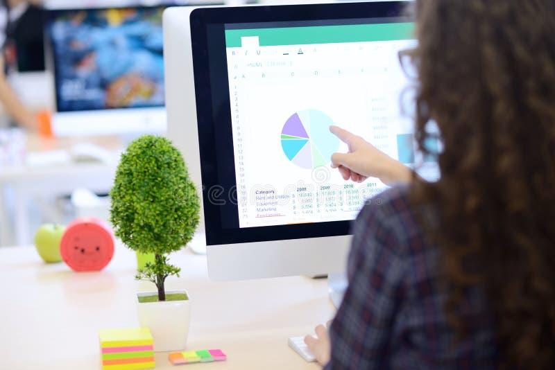 Über der Schulteransicht einer Geschäftsfrau, die am Computer arbeitet und auf Diagramm zeigt stockfoto