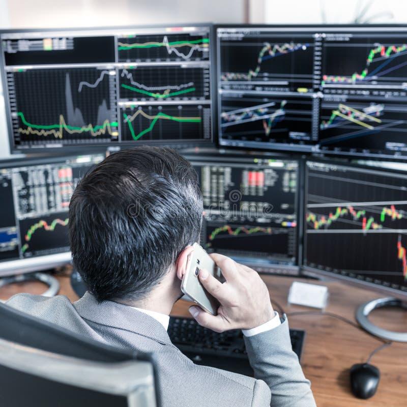 Über der Schulteransicht von den Bildschirmen und Börsenmakler, die online handeln stockfotos