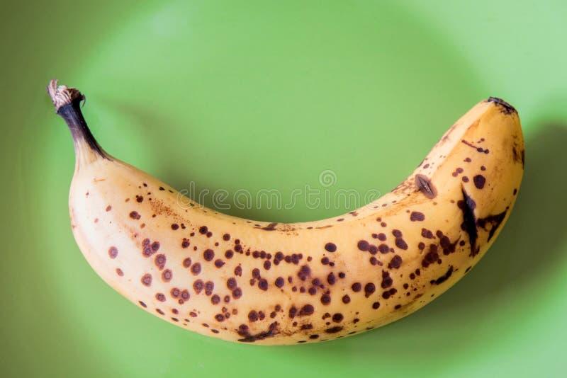 Über reife Banane auf grüner Platte stockfotografie