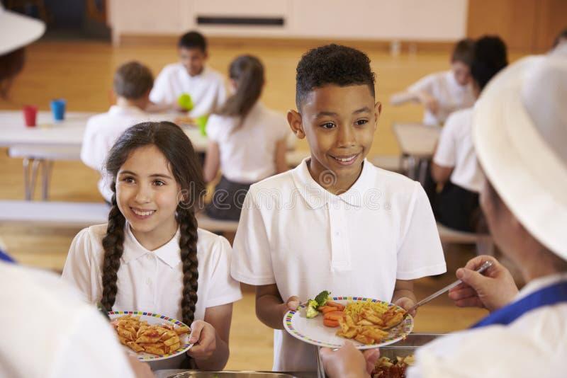 Über Schulteransicht von den Kindern, die in der Schulcafeteria gedient werden stockbilder