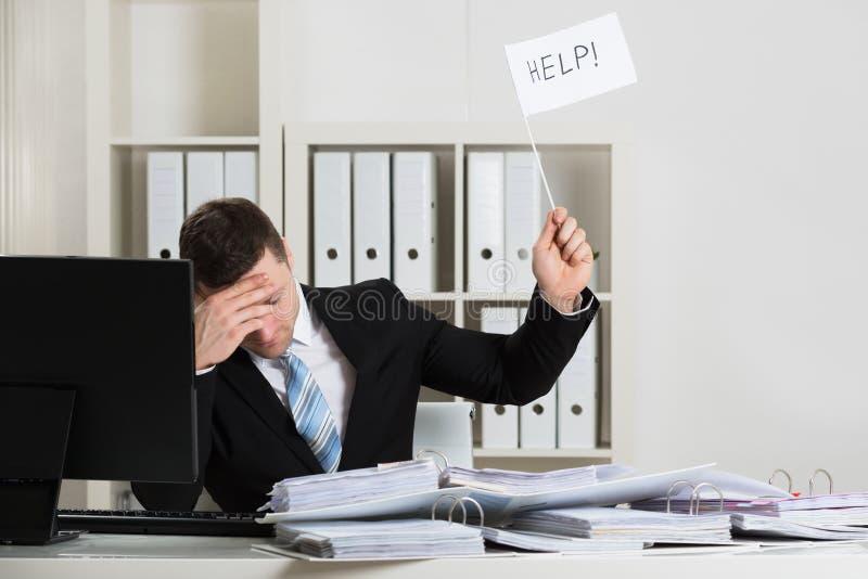 Überarbeiteter Buchhalter Holding Help Sign am Schreibtisch stockfotografie