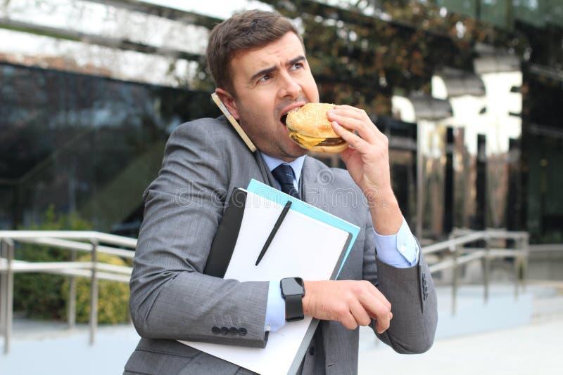 Überarbeiteter Geschäftsmann, der den Schnellimbiß unterwegs isst stockbilder
