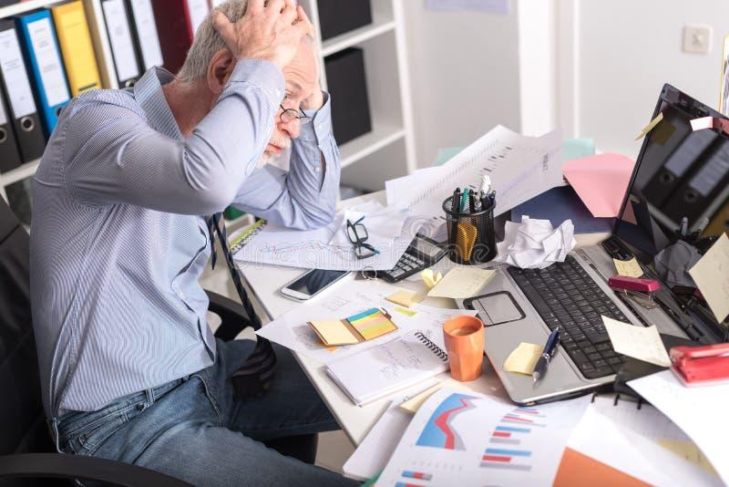 Überarbeiteter Geschäftsmann, der an einem unordentlichen Schreibtisch sitzt lizenzfreie stockfotografie