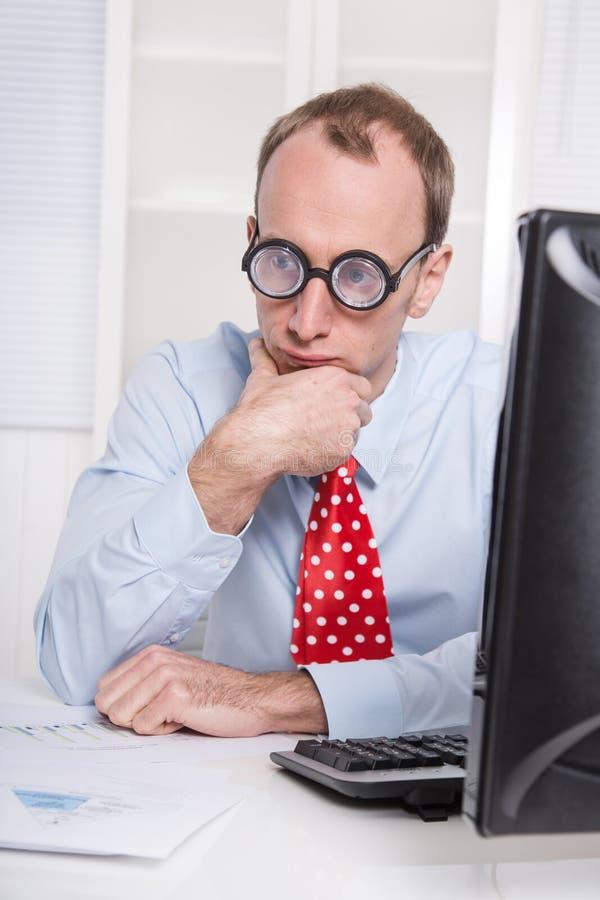 Überarbeiteter Geschäftsmann mit Gläsern anstarrend in Raum entlang des Schreibtisches - stockfotografie