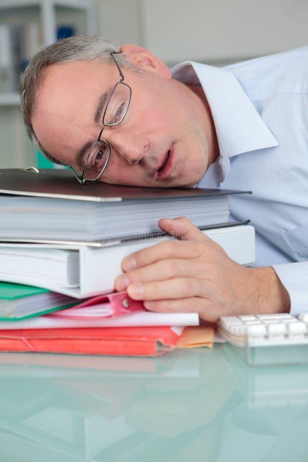 Überarbeiteter müder Geschäftsmann im Büro schlafend am Schreibtisch stockbilder