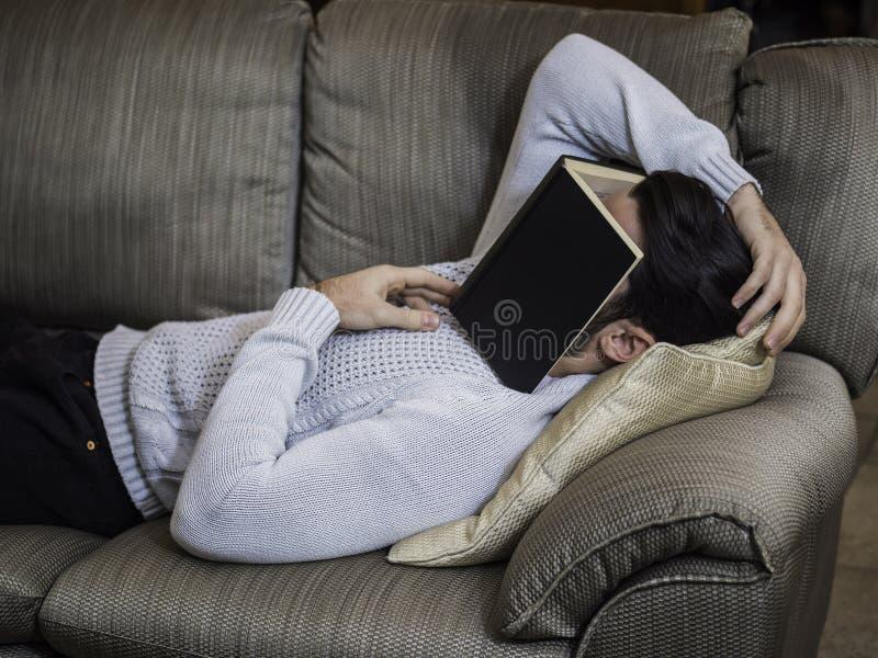 Überarbeiteter, müder junger Mann zu Hause, der unter Buch schläft lizenzfreie stockbilder