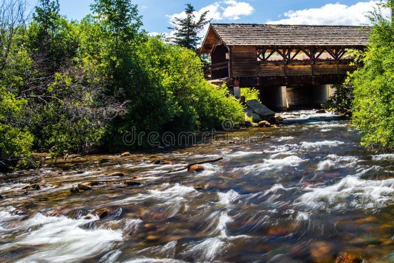 Überdachte Brücke über Flussstrom stockfotos