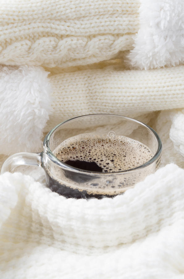 Überfallen Sie mit dem heißen Kaffee, der in einem weißen woolen Schal eingewickelt wird stockfoto