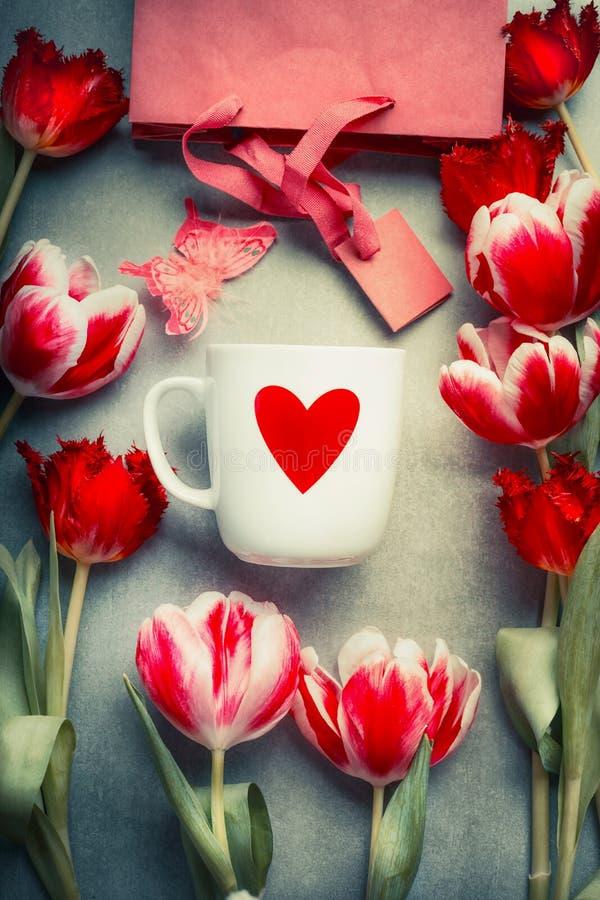 Überfallen Sie mit rotem Herzen, frischen Tulpenblumen und Einkaufstasche, Draufsicht Abstrakte Liebe und Gruß stockbild