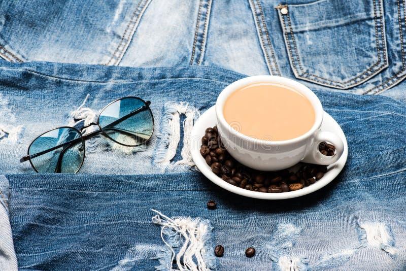 Überfallen Sie voll vom Kaffee mit Milch und Sonnenbrille auf Jeans, defocused Mann, der eine Kaffeepause nimmt Schale mit Kaffee stockbild
