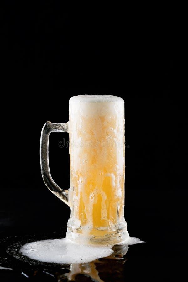 Überfließender Becher frisches Kaltlichtbier mit dem Schaum, der auf dem Tisch fließt und schönes verschüttetes Bier auf einem sc lizenzfreie stockbilder