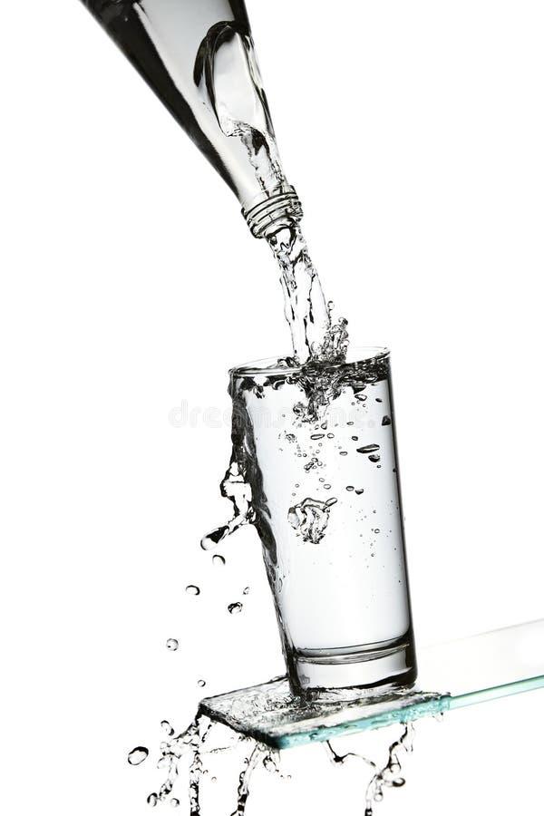 Überfließendes Glas Wasser lizenzfreies stockbild