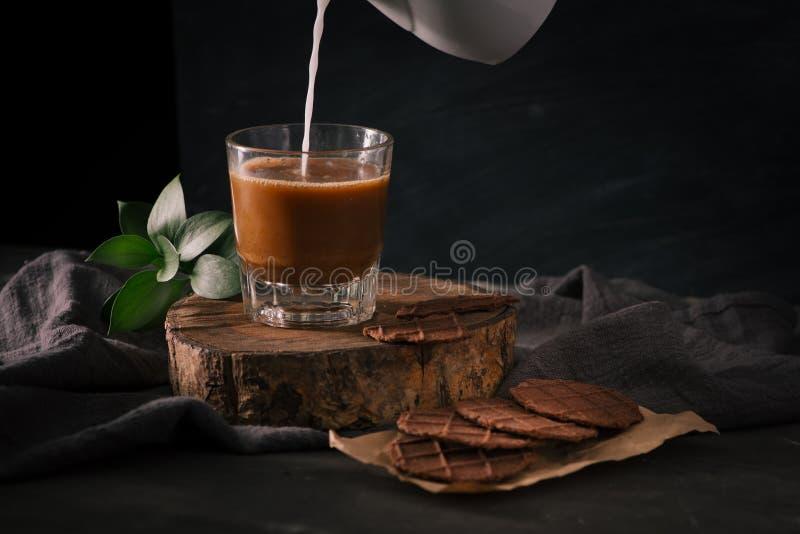 Übergeben Sie auslaufende Milch in Tasse Kaffee mit sortierten Plätzchen im Br lizenzfreies stockbild