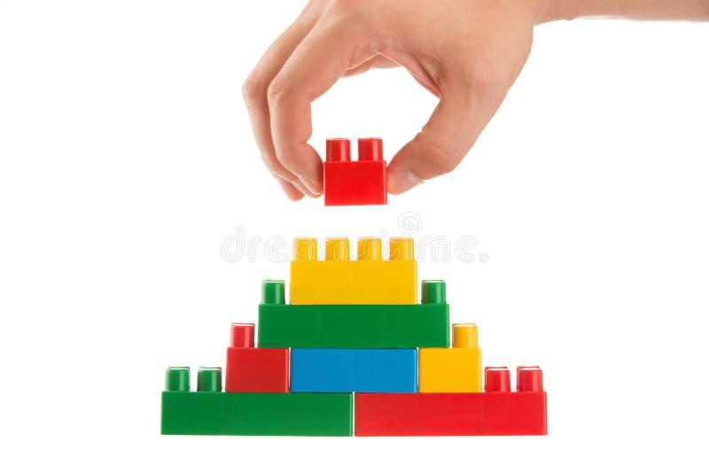Übergeben Sie das Aufbauen einer Wand, indem Sie herauf lego, Geschäftskonzeption stapeln lizenzfreies stockbild